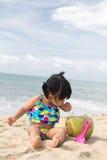 Asian baby girl on beach. Asian baby girl with coconut fruit on beach Royalty Free Stock Photos
