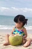Asian baby girl on beach. Asian baby girl with coconut fruit on beach Stock Photos