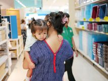 Asian baby girl being carried by her mother in a supermarket - baby refuses to walk royalty free stock image