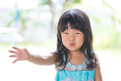 Asian baby girl in blue dress, on white and green background. Stock Photography