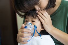 Asian baby girl breathing treatment with mother take care, at ro. Om hospital, close up health care kid concept sunny light background Stock Photography
