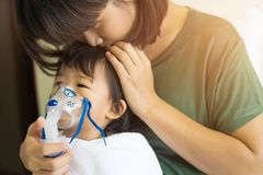 Asian baby girl breathing treatment with mother take care, at ro. Om hospital, close up health care kid concept sunny light background Royalty Free Stock Images