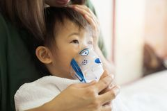Asian baby girl breathing treatment with mother take care, at ro. Om hospital, close up health care kid concept sunny light background Stock Photo