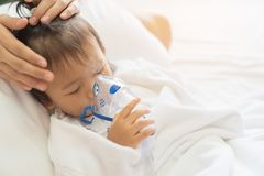 Asian baby girl breathing treatment with mother take care, at ro. Om hospital, close up health care kid concept sunny light background Stock Image