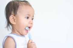 Asian baby girl brushing her teeth Stock Images