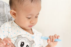 Asian baby girl brushing her teeth with mother Stock Images