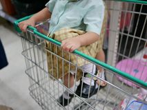 Asian baby girl climbing a shopping trolley in a supermarket stock image