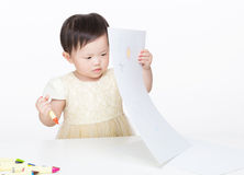 Asian baby girl concentrate on drawing. On white Royalty Free Stock Photo
