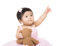 Asian baby girl with doll and pointing up Stock Image