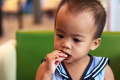Asian baby girl eating chocolate Royalty Free Stock Images