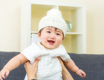 Asian baby girl embraced by parent. At home Royalty Free Stock Photography
