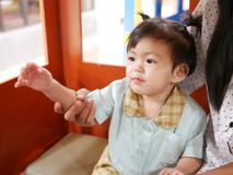 Asian baby girl enjoy having her mother teaching her to wave her hand royalty free stock images