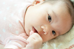 Asian baby girl laying on bed. And looking Royalty Free Stock Image