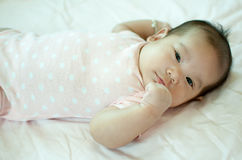 Asian baby girl laying on bed. And smiling Royalty Free Stock Photography