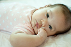 Asian baby girl laying on bed Stock Photo