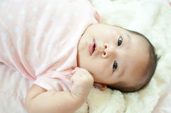 Asian baby girl laying on bed. And smiling Stock Images