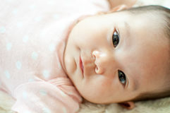 Asian baby girl laying on bed. And smiling Royalty Free Stock Images
