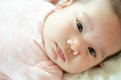 Asian baby girl laying on bed. And smiling Royalty Free Stock Image