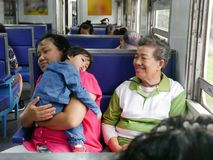Asian baby girl leaning on her auntie`s shoulder with her grandmother sitting next to during a trip by train royalty free stock photos