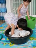 Asian baby girl left soaking clothes in water to wash them stock image