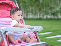 Asian baby girl look joyful sitting in stroller. Royalty Free Stock Image