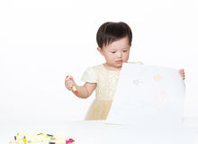 Asian baby girl looking at the picture. Isolated on white Royalty Free Stock Photo