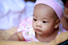 Asian baby girl lying on bed Royalty Free Stock Image