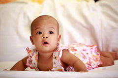 Asian baby girl lying on bed Stock Photos