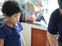 Asian baby girl looking at her auntie preparing cooking ingredients royalty free stock photos