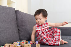 Asian baby girl play toy block and sitting on sofa at home Royalty Free Stock Photography