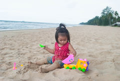 Asian baby girl playing on the beach. Royalty Free Stock Photography