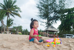 Asian baby girl playing on the beach. Stock Photo