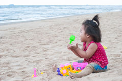 Asian baby girl playing on the beach. Stock Images