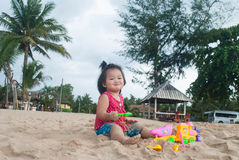 Asian baby girl playing on the beach. Royalty Free Stock Images