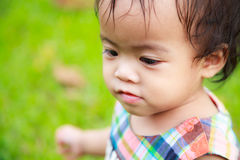 Asian baby girl playing in grass field Stock Photos