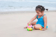 Asian baby girl playing with the sand on the beach. Royalty Free Stock Image