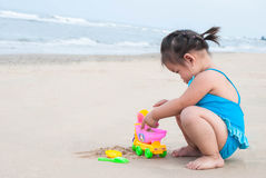 Asian baby girl playing with the sand on the beach. Royalty Free Stock Images