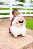 Asian baby girl ride sheep statue Royalty Free Stock Photos