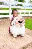 Asian baby girl ride sheep statue Royalty Free Stock Photos