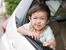 Asian baby girl in a school uniform smiling in a car ready to go to school in the morning royalty free stock photo