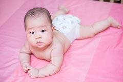 Asian baby girl scowl on pink bed. And she looking at the camera Royalty Free Stock Images