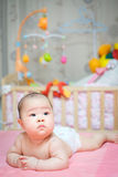 Asian baby girl scowl and tongue out. She overturn on pink bed whit her toys in blackground Royalty Free Stock Photo