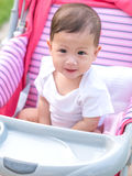 Asian baby girl smiling and look joyful sitting in stroller. Royalty Free Stock Photo