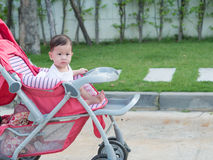 Asian baby girl smiling and look joyful sitting in stroller. Royalty Free Stock Photos