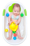 Asian baby girl taking a bath in white tub and playing duck Royalty Free Stock Photo