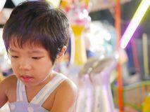 Asian baby girl taking a roundabout / carousel at a fair royalty free stock photography