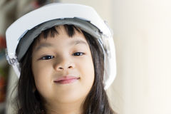 Asian baby girl is wearing Engineering safety hat. Asian baby girl is wearing Engineering white safety hat Stock Photos