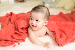 Asian baby girl is wrapped in orange blanket Royalty Free Stock Image