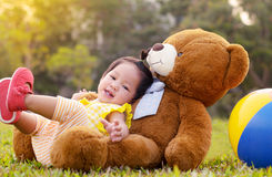 Asian baby happy in grass in moring time with sunlight. Royalty Free Stock Images