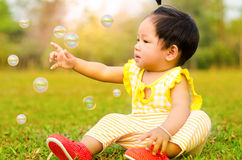 Asian baby happy in grass in moring time with sunlight. Stock Photo